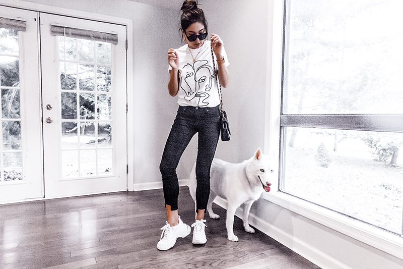 fashion blogger and her dog white husky featuring face t-shirt, chunky sneakers and skinny jeans