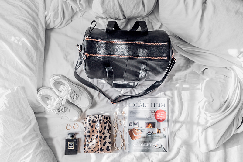 flatlay style with leather duffle bag and chunky sneakers