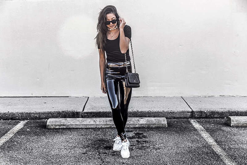 luxury fashion blogger wears a luxury bag, velvet bodysuit and vinyl leather leggings with chunky sneakers
