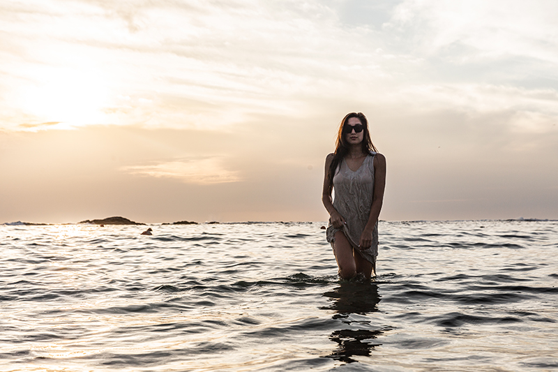 travel blogger in the sea with minimal golden backdrop