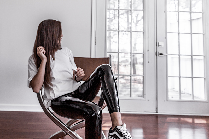fashion girl relaxing in basic white tshirt and vinyl leggings