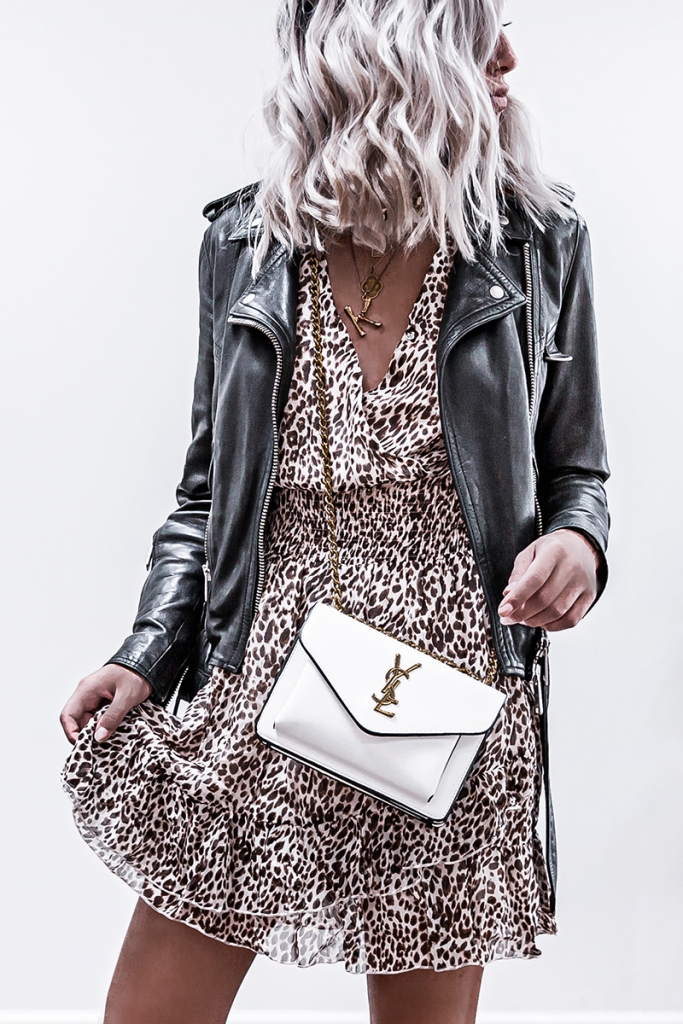 luxury fashion blogger in leopard print dress, all saints biker jacket and luxury ysl handbag