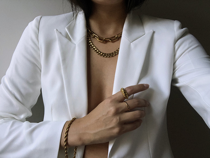 white blazer with gold chain necklaces